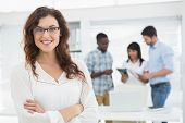 image of arms race  - Smiling businesswoman with arms crossed in front of her colleagues - JPG