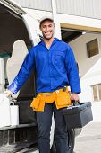 Smiling handsome handyman holding toolbox in front of his van