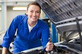 Smiling mechanic fixing car engine at the repair garage