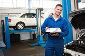Smiling mechanic looking at camera at the repair garage