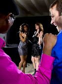 stock photo of soliciting  - two pickup artists harrassing women at a nightclub - JPG
