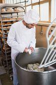 Baker preparing dough in industrial mixer at the bakery