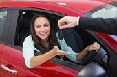 Businessman holding car keys by his fingertips at new car showroom