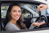 Salesman giving keys to a smiling woman at new car showroom