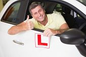 Man gesturing thumbs up holding a learner driver sign at new car showroom