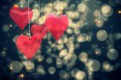 Love hearts against shimmering light design on black