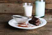Glass and bottle of milk with chocolate chunks on plat with strainer of cocoa on rustic wooden planks background