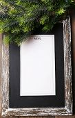 Menu board with Christmas decoration on wooden planks background