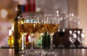 Glasses of wine on counter and bar on background