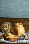 Tasty sandwich and jar with fresh peanut butter on wooden background