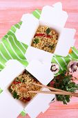 Chinese noodles and sticks in takeaway boxes on green napkin on pink background