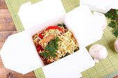 Chinese noodles in takeaway box on mat background