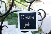 Signboard with Dream Job text on it hanging on metal fence