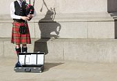 Scottish Man In Kilt Playing Bagpipes