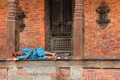 KATHMANDU, NEPAL - APRIL 2014 : A Nepalese woman resting at the temple at Kathmandu Durbar Square in Kathmandu, Nepal on 12 April 2014.