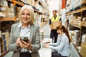 Smiling warehouse manager using handheld in a large warehouse