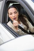 Pretty businesswoman using wing mirror to put on lipstick in her car