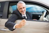foto of showrooms  - Smiling man holding car keys while sitting on a car at new car showroom - JPG