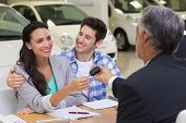 stock photo of showrooms  - Salesman giving car keys to a couple at new car showroom - JPG