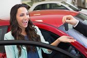 Excited woman receiving car key at new car showroom