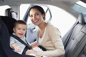 image of pretty-boy  - Mother securing her baby in the car seat in her car - JPG