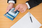 Businessman working on his finances at his desk in his office