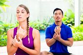 Mixed Asian and Caucasian couple at yoga training in tropical Asia