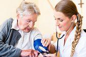 Nurse measuring blood pressure at senior woman patient in retirement home