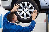 picture of garage  - Mechanic adjusting the tire wheel at the repair garage - JPG