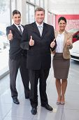 Smiling business team standing while giving thumbs up at new car showroom