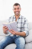 Smiling man sitting in the sofa reading a book