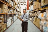 pic of warehouse  - Smiling warehouse manager writing on clipboard in a large warehouse - JPG