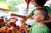 image of farmers market vegetables  - Cute boy with his mother buying fresh vegetables at the farmer - JPG