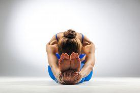 stock photo of yoga  - young beautiful yoga posing on a studio background - JPG