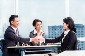 image of candid  - Asian recruitment team hiring candidate in job interview - JPG