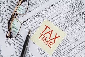 picture of time-saving  - CLoseup of a text of tax time on the paper note with tax form glasses and pen - JPG