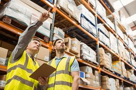 image of thoughtfulness  - Warehouse manager and foreman working together in a large warehouse - JPG
