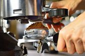 stock photo of dispenser  - Barista dispensing ground coffee from a grinder into a portafilter - JPG