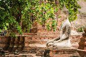 stock photo of gautama buddha  - Old Buddha Statue and Old Temple Architecture at Wat Mahathat Ayutthaya Thailand World Heritage Site - JPG