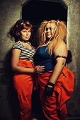image of lockups  - Two pretty girls in orange clothes posing over metallic wall of their prison cell - JPG