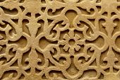 stock photo of carving  - Relief wall carving from the ancient palace and fortress of Alhambra in Granada Spain makes a carving background - JPG