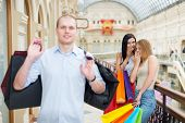 picture of snickers  - Smiling girls and a man with shopping bags in a luxury central shop - JPG