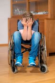 stock photo of sad boy  - disabled boy in wheelchair at home is sad - JPG