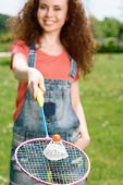 stock photo of shuttlecock  - Portrait of a young beautiful lady standing in a park stretching a racquet in front of her with a shuttlecock on it - JPG