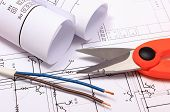 foto of electrical engineering  - Cable cutter electric wire and rolls of electrical diagrams lying on construction drawing of house accessories for engineer jobs - JPG