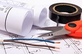 image of electrical engineering  - Cable cutter electric wire and black insulating tape rolls of electrical diagrams lying on construction drawing of house accessories for engineer jobs - JPG