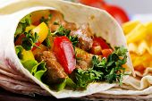 picture of potato chips  - Homemade tasty burrito with vegetables and potato chips on cutting board - JPG