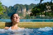 stock photo of relaxing  - Beautiful relaxed woman enjoying spa pool at resort in Thailand - JPG