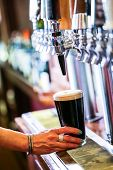 picture of draft  - Bartender pouring draft beer in the bar. ** Note: Shallow depth of field - JPG