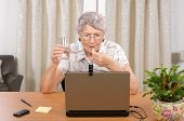 picture of antidepressant  - Senior glasses woman is taking antidepressant pill during reading bad news on the Internet - JPG